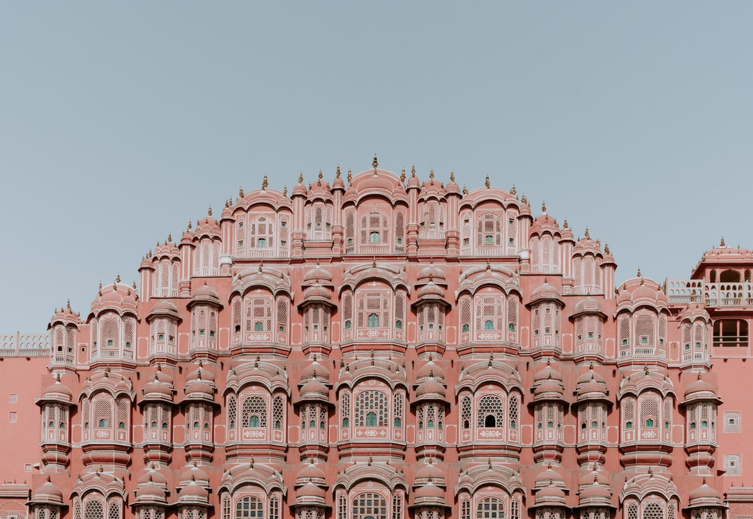 Several tall buildings in the background with Hawa Mahal in the background