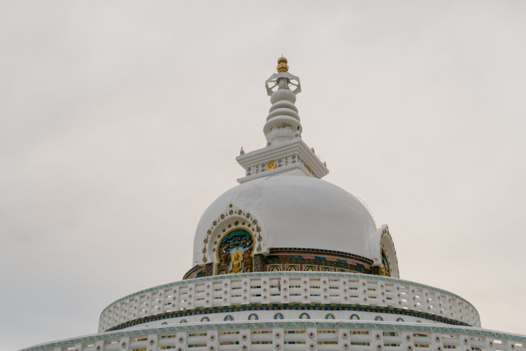 A large building with Shanti Stupa in the background