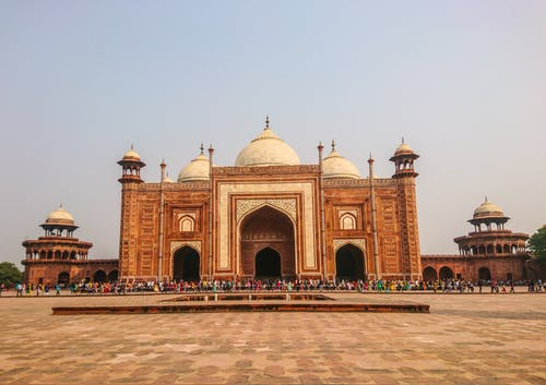 A large stone building with Taj Mahal in the background